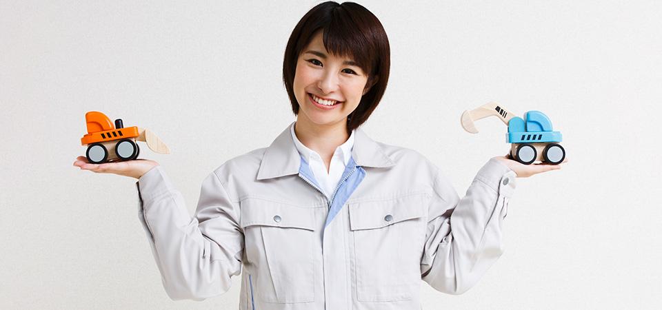 女性作業員と重機の模型